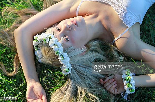 woman with blond hair lying down on grass - lying down stock-fotos und bilder