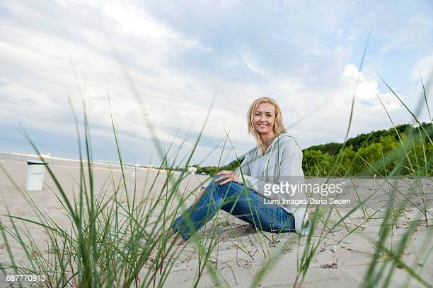 Woman with blond hair relaxing on sandy beach