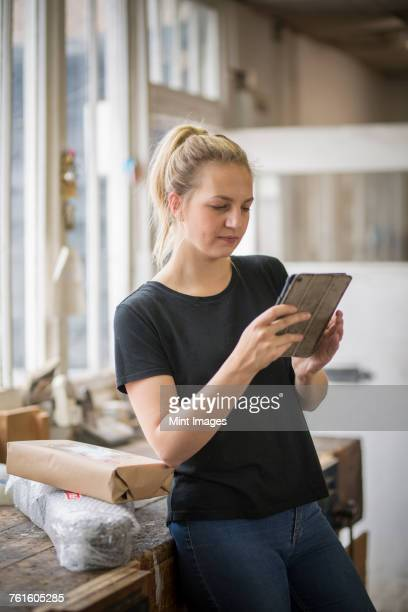 Woman with blond hair standing in a workshop using a digital tablet, wrapped parcels on a table.