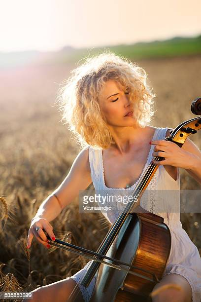 Woman with blonde curly hair playing cello in wheat field