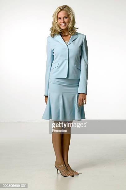 Woman with blonde hair wearing blue dress, posing in studio, portrait