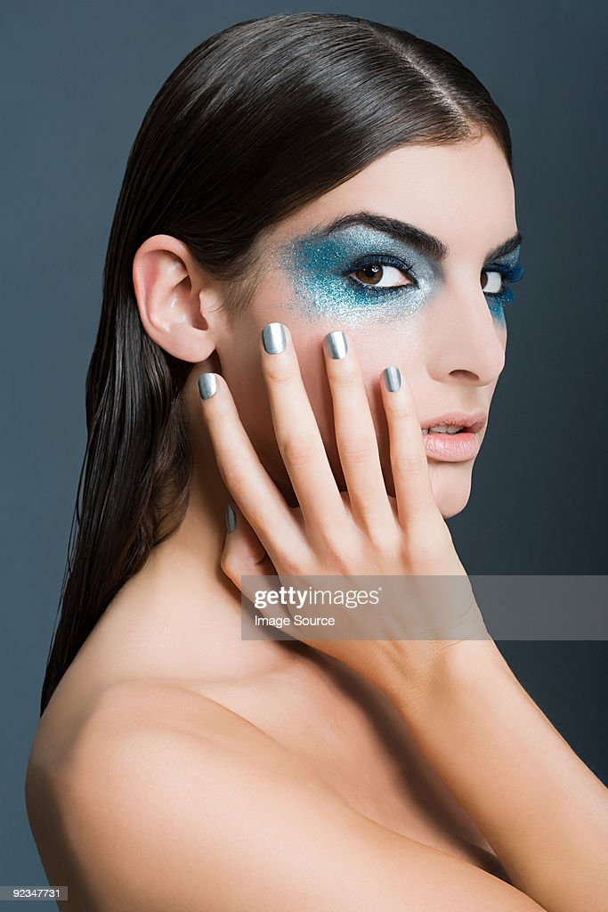 Woman with blue glitter eye makeup : Stock Photo