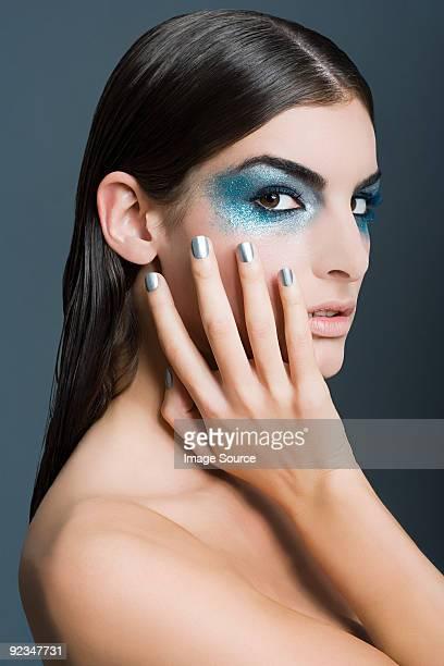 Frau mit blauen Augen Make-up mit Glitzerelementen