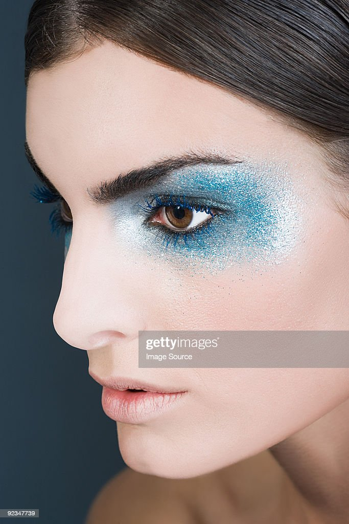 Woman with blue glitter eye makeup : Stock Photo
