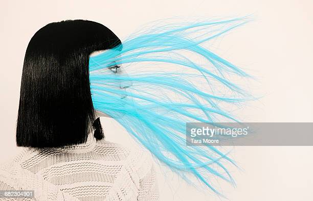 woman with blue hair covering face