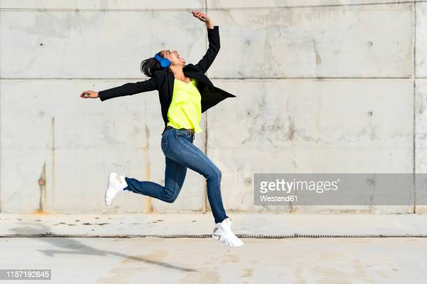 woman with blue headphones listening music, jumping in the air and taking a selfie - excitement stock pictures, royalty-free photos & images