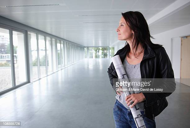 Woman with blue prints, in an empty room