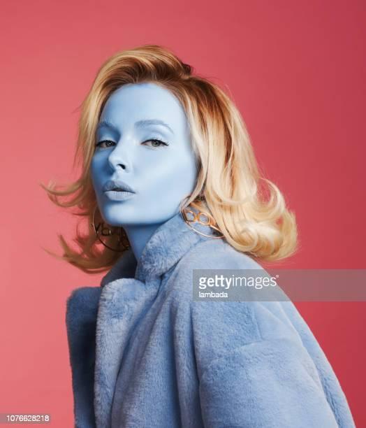 frau mit blauer haut tragen blaue mantel - außerirdischer stock-fotos und bilder
