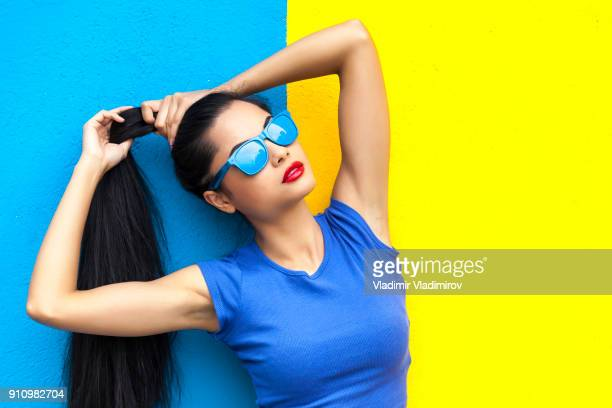 Woman with blue sunglasses in front of colorful wall