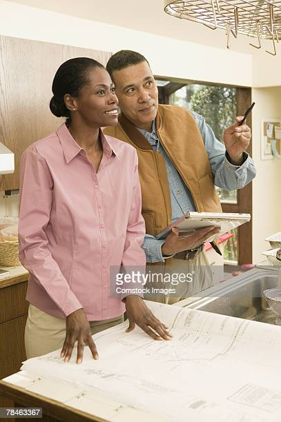 Woman with blueprints and inspector gesturing