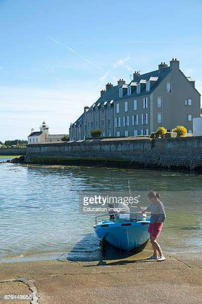 Woman with boat quayside Barfleur Normandy France