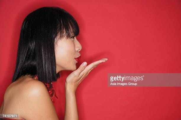 Woman with bob haircut, blowing a kiss, side view