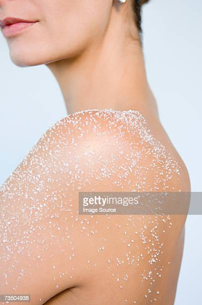 Woman with body scrub on shoulder