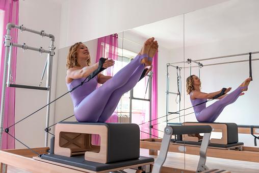 Woman With Bodysuit Exercising on Pilates Machine - gettyimageskorea