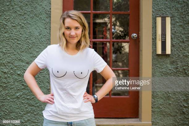 woman with boob tee shirt standing outside her apartment door with hands on her hips smirking - woman flat chest stock photos and pictures
