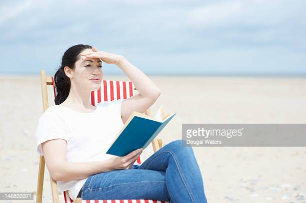 Woman with book looking out across beach.