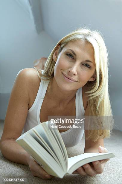 Woman with book smiling, portrait, close-up