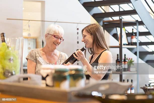 woman with bottle of wine smiling - sigrid gombert stock-fotos und bilder