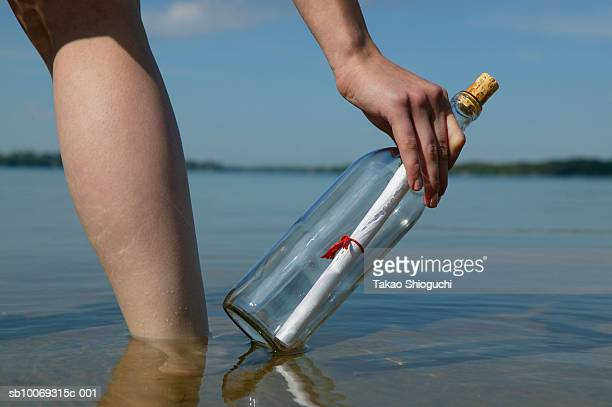 woman with bottle on beach - contea di prince edward ontario foto e immagini stock