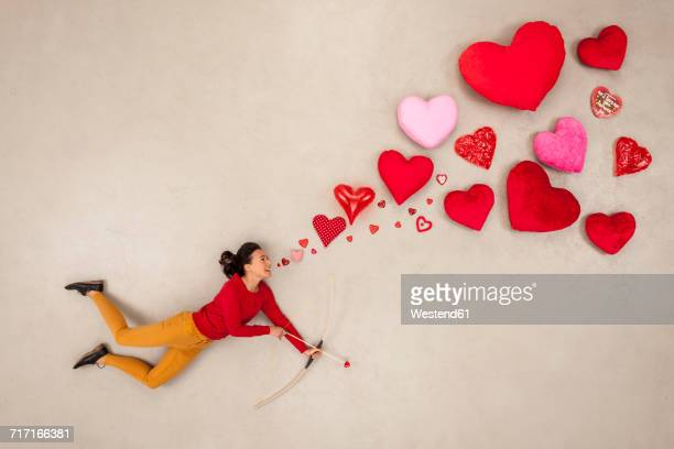 woman with bow and arrow and hearts around - cupid stock pictures, royalty-free photos & images