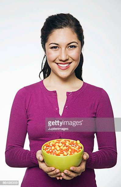 woman with bowl of candy corn - candy corn stock photos and pictures