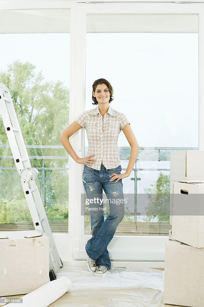 Woman with boxes in apartment, smiling : Stock Photo