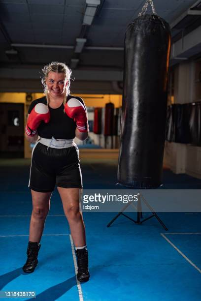 woman with boxing gloves standing in combat pose in a health club - mixed martial arts stock pictures, royalty-free photos & images