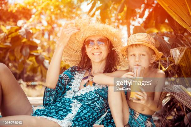 Woman with boy drinks fresh juice on the beach