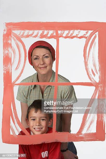 woman with boy (6-7 years) standing behind transparent painting of window on glass, studio shot, portrait - 6 7 years stock pictures, royalty-free photos & images