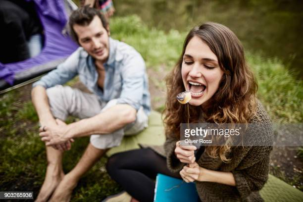 woman with boyfriend eating roasted marshmallow at a tent - essen mund benutzen stock-fotos und bilder