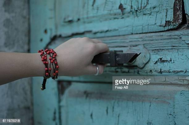 Woman with bracelet opening the door