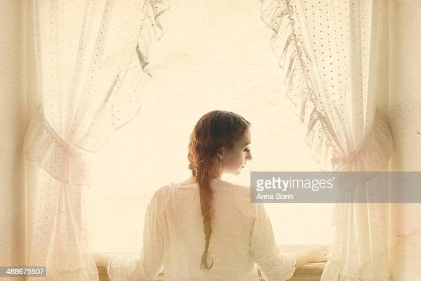Woman with braid at window framed by curtains