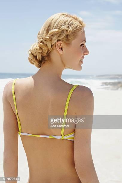 Woman with braided hair in bikini on beach