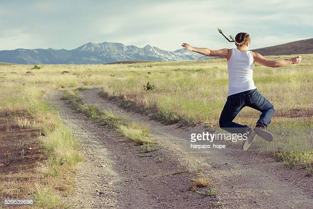 woman with braids jumping on a rural road. - human foot stock pictures, royalty-free photos & images