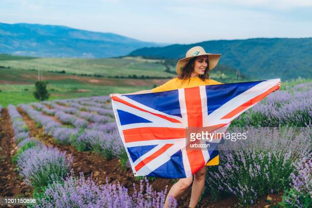 woman with british flag in field - purple dress stock pictures, royalty-free photos & images