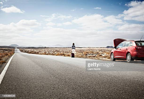 Woman with broken down car on rural road