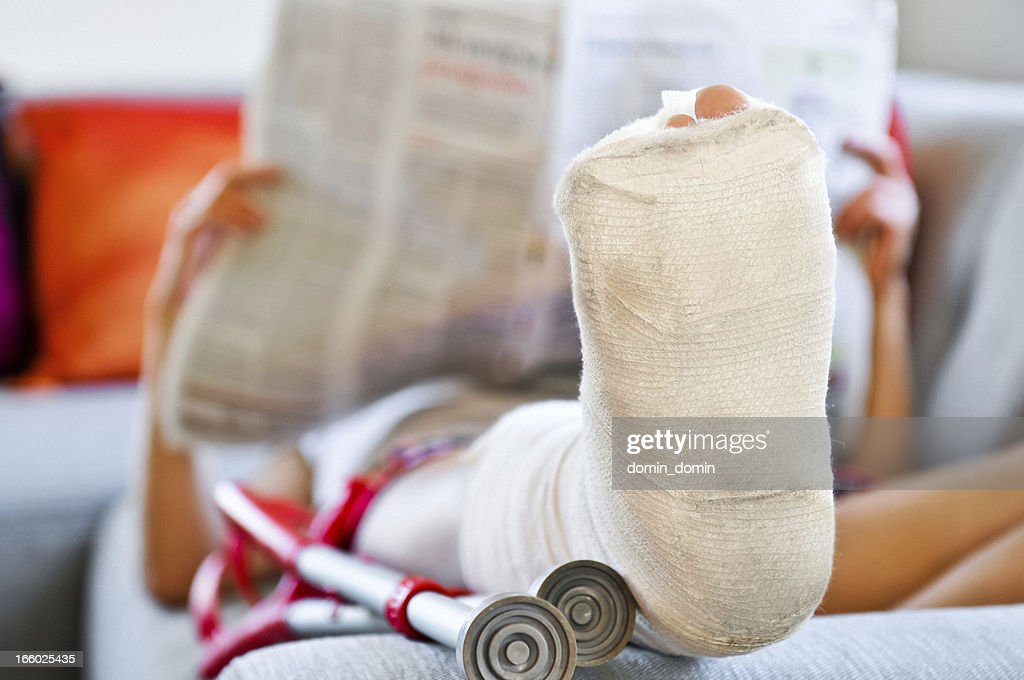 Woman with broken leg lying on sofa and reading newspaper : Stock Photo