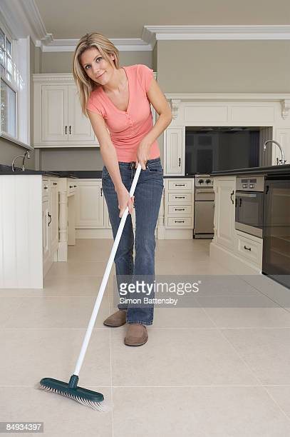 woman with broom in kitchen