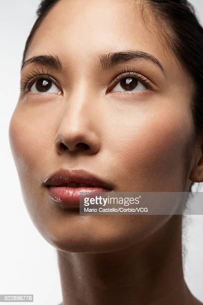 woman with brown eyes looking up - wishful skin stock pictures, royalty-free photos & images
