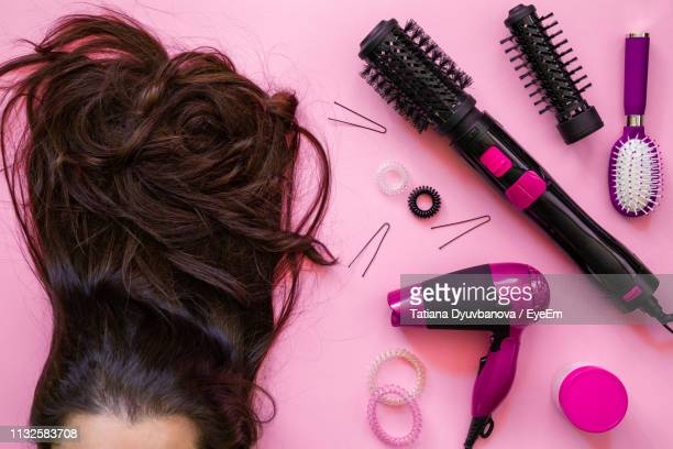 woman with brown hair by personal accessories on table - secador de cabelo - fotografias e filmes do acervo