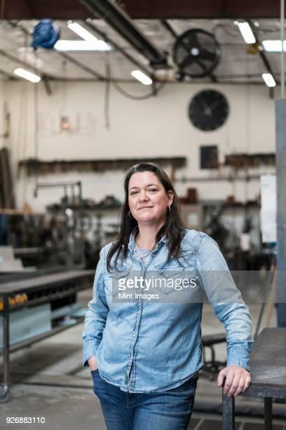 Woman with brown hair wearing Denim shirt standing in metal workshop, smiling at camera.
