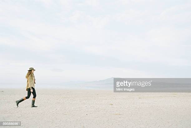 Woman with brown, long and curly hair walking through a desert plain, wearing a hat and leather boots.