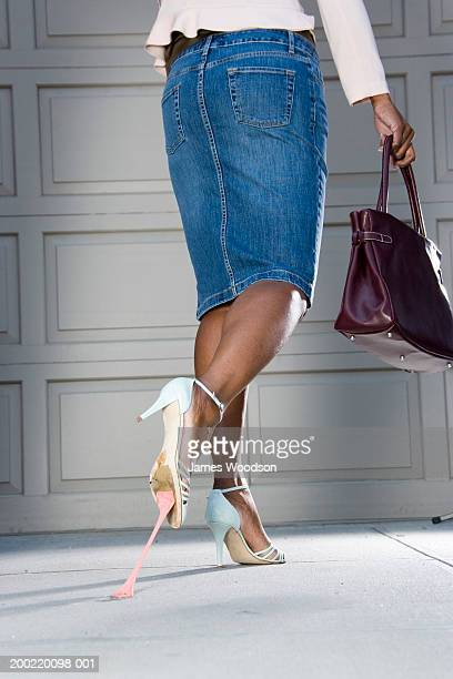 Woman with bubblegum stuck on bottom of shoe, low section, rear view