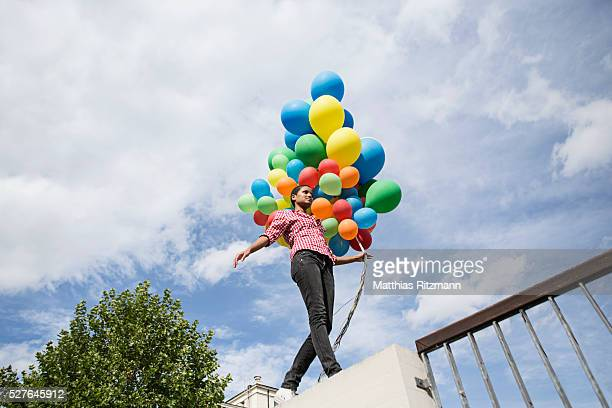 Woman with bunch of colorful balloons walking on fence