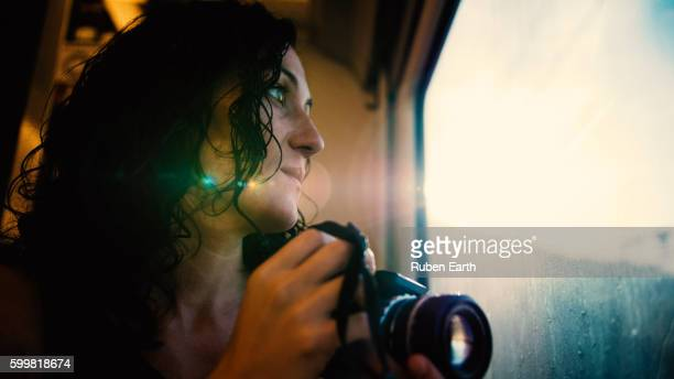 Woman with camera looking through the window
