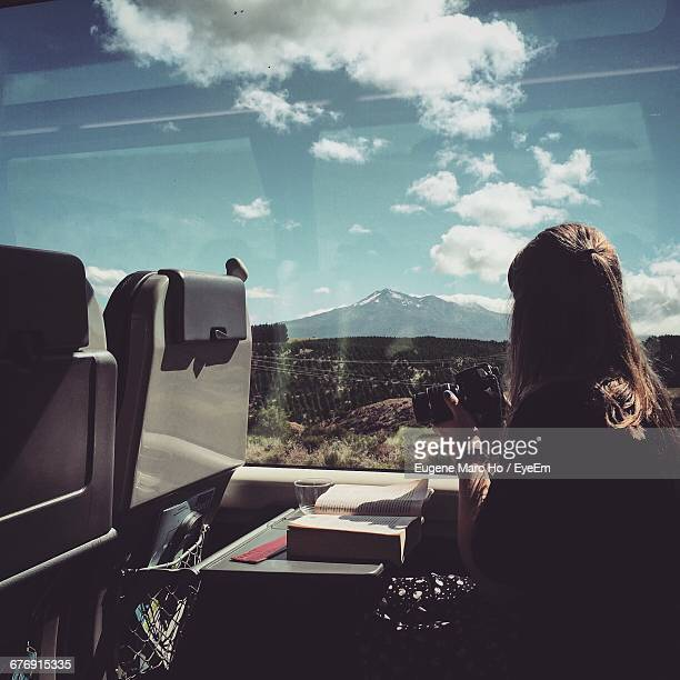 woman with camera sitting in train while looking at mountain - bahnreisender stock-fotos und bilder