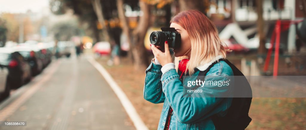 Woman with camera taking picture in the street : Stock Photo