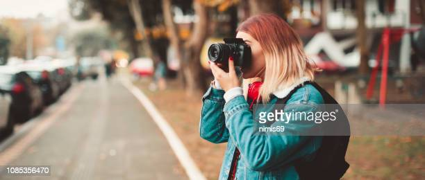 woman with camera taking picture in the street - photographer stock pictures, royalty-free photos & images
