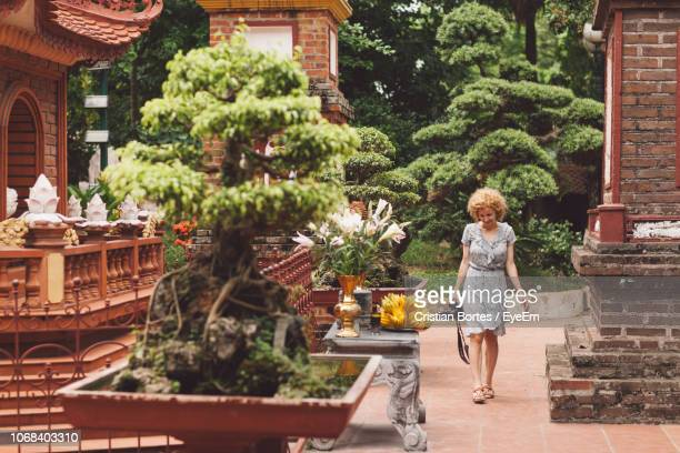 woman with camera walking on footpath at temple - bortes stock pictures, royalty-free photos & images