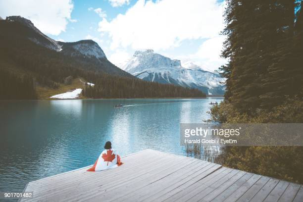 woman with canada flag sitting on pier by river - canadian flag stock pictures, royalty-free photos & images